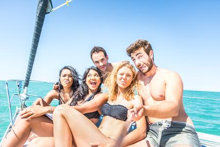 personas saltando: Grupo de amigos que toman autofoto desde el barco - los jóvenes multiétnicos divertirse y fiesta en un barco de vela Foto de archivo
