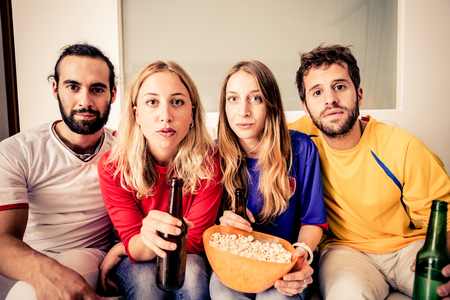 thriller: Young attractive people watching TV at home - Group of friends looking at something dramatic on television Stock Photo