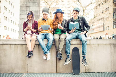 in a row: Group of teenagers making different activities sitting in an urban area - Friends hanging out outdoors Stock Photo