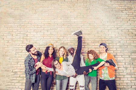 Grupa portret wieloetnicznego chłopców i dziewcząt z kolorowe modne ubrania gospodarstwa przyjaciela w rękach i stwarzających na ścianie z cegły - styl ludzi miejskie zabawy, studio shot - Pojęcia o młodzieży i wspólnoty