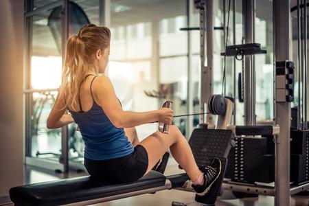 체육관에서 무게 기계와 그녀의 허리와 어깨를 훈련하는 여자