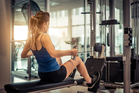 équipement: Femme formation son dos et l'épaule avec la machine de poids dans un gymnase