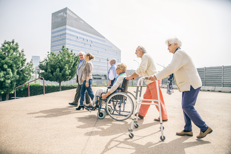Group of senior people with some diseases walking outdoors - Mature group of friends spending thier time together Standard-Bild
