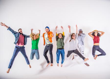 Groupe multi-ethnique d'amis de sauter sur fond blanc, tourné en studio