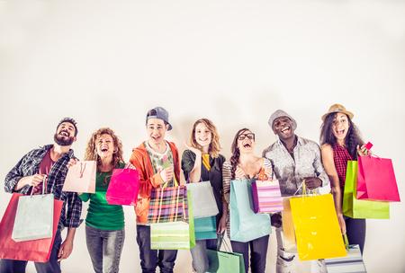 grupo multiétnico de la gente con sus bolsas de compras coloreados y riendo - Retrato de amigos divertidos que presenta en el fondo blanco