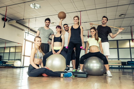 athletic wear: Group of sportive people in a gym - Happy sporty friends in a weight room while training - Concepts about lifestyle and sport in a fitness club