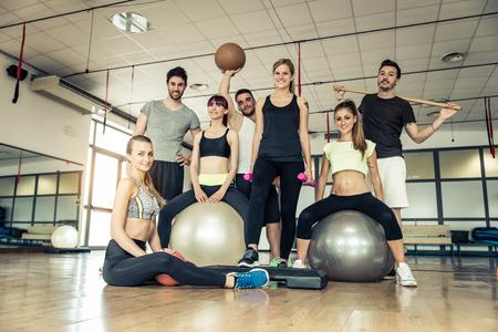 Grupo de personas deportivas en un gimnasio - amigos deportivo felices en una sala de pesas mientras formación - Conceptos sobre el estilo de vida y el deporte en un club de fitness