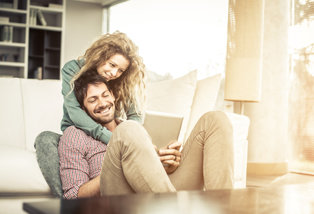 Couple of lovers at home watching the smartphone on the couch - Man and woman relaxing of the sofa, woman leaning head on her boyfriends shoulder