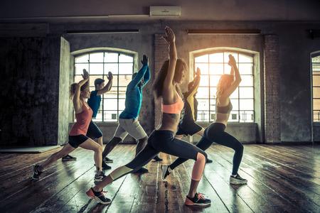 체육관 훈련에서 낚시를 좋아하는 사람들의 그룹 - 운동 세션을 시작하기 전에 스트레칭 운동 선수의 multiracial 그룹