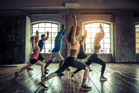 Groupe de personnes sportives dans une formation gymnase - Groupe multi-ethnique des athlètes d'étirement avant de commencer une séance d'entraînement Banque d'images - 57814540