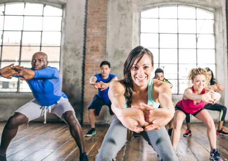 gimnasia aerobica: grupo multiétnico de la formación de personas en un gimnasio - Formador y personas deportivos haciendo sentadillas en una clase de gimnasia