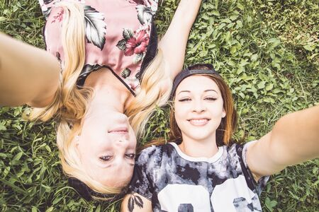 girl lying down: Two pretty young girls holding camera and taking a selfie - Best teen friends having fun outdoors with modern technology Stock Photo