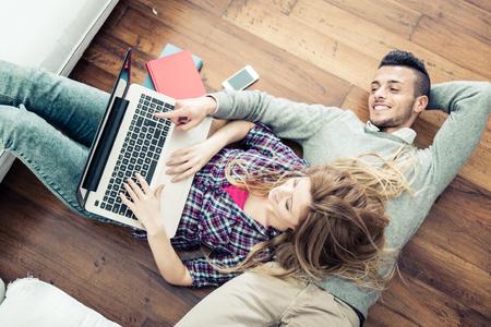 -リビング ルームでノートブックのビデオを見て二人の若い友人のラップトップ コンピューターでのオンライン ショッピングのカップルを上から表示します。