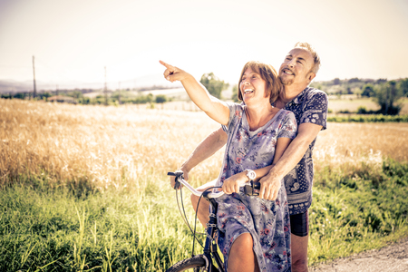 Middle age couple going for a ride with the bicycle in the countryside - Senior couple having fun outdoors 스톡 콘텐츠