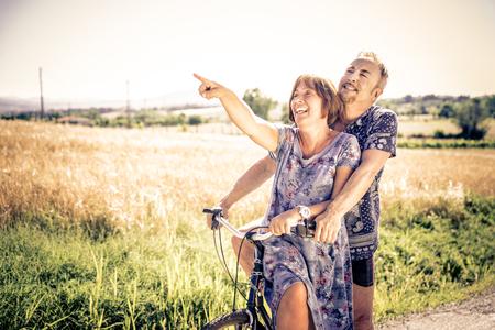 Para w średnim wieku idzie na jazdę z rowerem na wsi - Starszy para zabawy na wolnym powietrzu