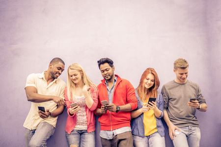 Мультикультурном группа друзей с помощью мобильных телефонов - студентов, сидящих в ряд и печатать на смартфоны Фото со стока