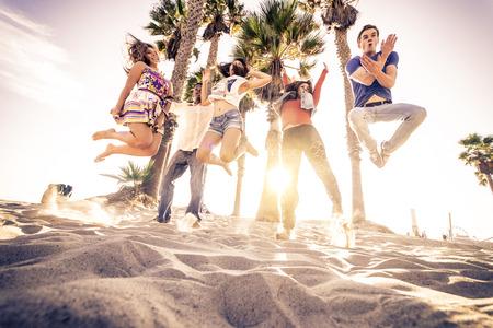 笑顔の友人のビーチでジャンプと楽しんで - 熱帯の島で党を持つ多民族若者のグループ