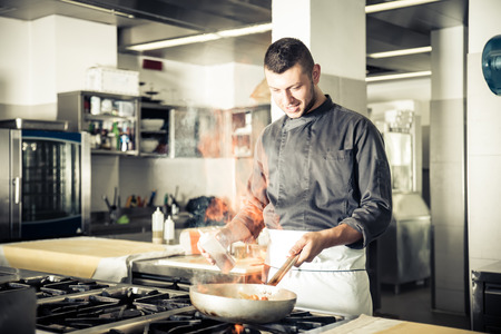 Chef in hotel or restaurant kitchen working and cooking - Chef in restaurant kitchen at stove with pan, doing flambe on food