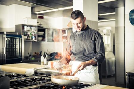 uniforme: Chef en el hotel o restaurante de cocina de trabajo y la cocina - Chef de cocina de un restaurante en la cocina con la cacerola, haciendo flameados en alimentos
