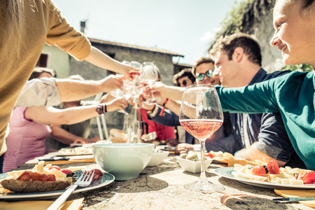host: Group of friends toasting wine glasses and having fun outdoors - People having lunch in a restaurant