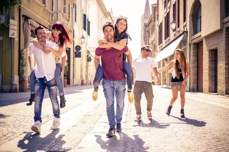 pareja de adolescentes: jóvenes amigos que se divierten al aire libre - Seis estudiantes al aire libre, hombres que llevan dos chicas en el de lengüeta Foto de archivo
