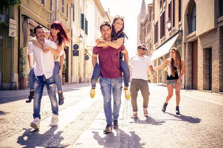 couple laughing: Young friends having fun outdoors - Six students outdoors, men carrying two girls on piggyback Stock Photo