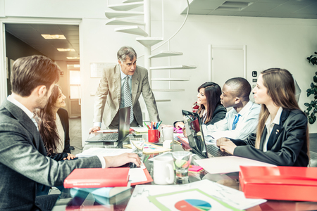 彼らの上司のスピーチ - シニア マネージャーの彼のチームと話を聞いてビジネスマンのグループ