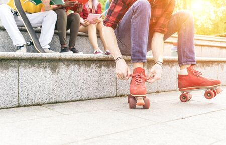lace up: Group of teenagers sitting on the stairs. Tying the roller skates lace up.