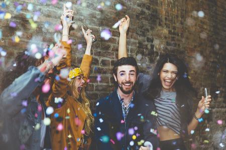 Un gruppo di quattro amici ridere ad alta voce esterna, la condivisione di buono e positivo stato d'animo. Fare festa all'aperto con champagne e coriandoli
