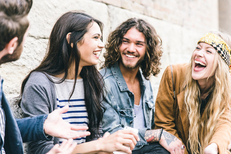 Groupe de quatre amis de rire à l'extérieur, le partage de bonnes fort et l'humeur positive
