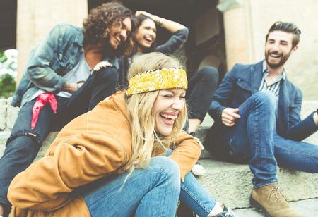 Grupo de quatro amigos rindo alto exterior, partilha de boas e humor positivo