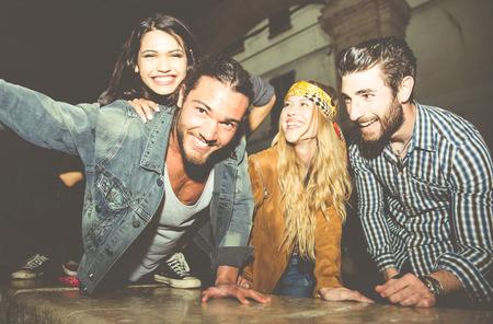 Gruppe von Freunden sitzen auf der Treppe und nehmen selfie. Spaß haben in der Nacht im Freien Standard-Bild