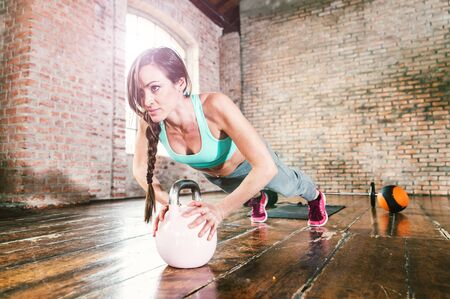 Woman training hard with push up exercise in her gym Banco de Imagens
