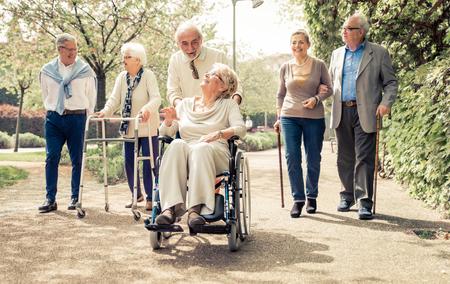 grupos de personas: Grupo de personas mayores que caminan al aire libre