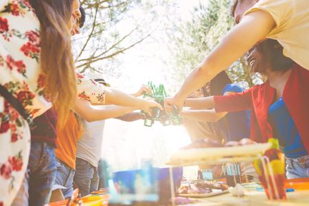 Amis faisant partie à la maison avec un barbecue. Tintement avec des bouteilles de bière Banque d'images - 60981675