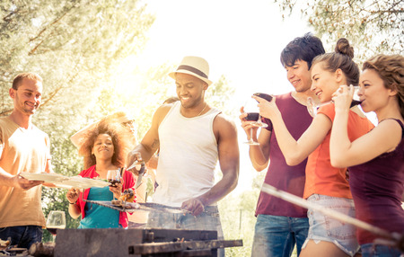 barbecue: Group of friends making barbecue in the nature. Eating and sharing positive emotions. Stock Photo