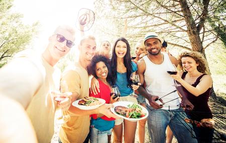 Groep vrienden het maken van een barbecue in de natuur. Het eten en het delen van positieve emoties Stockfoto