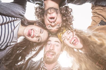 iluminado a contraluz: Grupo de amigos que hacen caras divertidas en la cámara