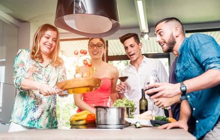 personas reunidas: Grupo de amigos haciendo fiesta de la pasta y que se divierte en la cocina