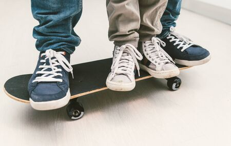 plimsoll: Father and son playing together on the skateboard. Teaching balance and playing together at home