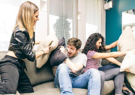 pijamada: Amigos que se divierten en el sof� y hacer pelea de almohadas. grupo de raza mixta de amigos que juegan en la sala de estar en casa