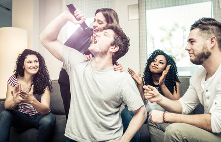 Group of friends playing hard with video games and karaoke. Having fun at home