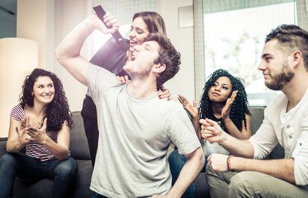 Groep vrienden spelen hard met videospelletjes en karaoke. Plezier thuis Stockfoto