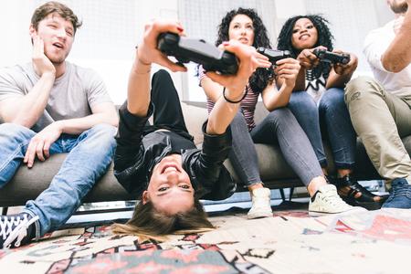 비디오 게임과 하드 재생 친구의 그룹입니다. 거실에 앉아서 함께 연주하는 젊은 사람들