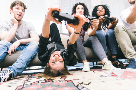 Grupo de amigos que juegan duro con los videojuegos. jóvenes sentados en la sala de estar y jugar juntos Foto de archivo - 60981721