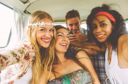 mujer hippie: hippie amigos que se divierten en una furgoneta de la vendimia, tomar buenas fotos