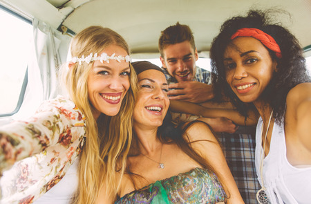 Hippie friends having fun into a vintage van, taking nice pictures