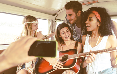 Hippie friends having fun into a vintage van, playing the guitar and singing songs