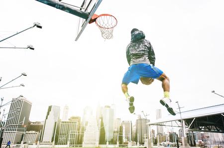 basketball dunk: Street basketball player performing an huge rear slam dunk. New york Manhattan buildings background