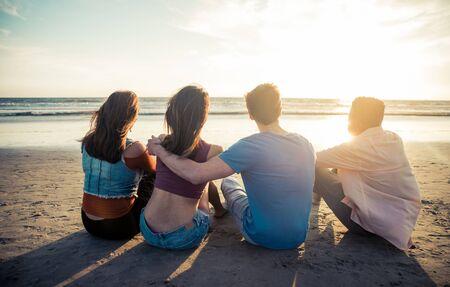 gente sentada: Cuatro amigos disfrutando de la puesta de sol en la playa